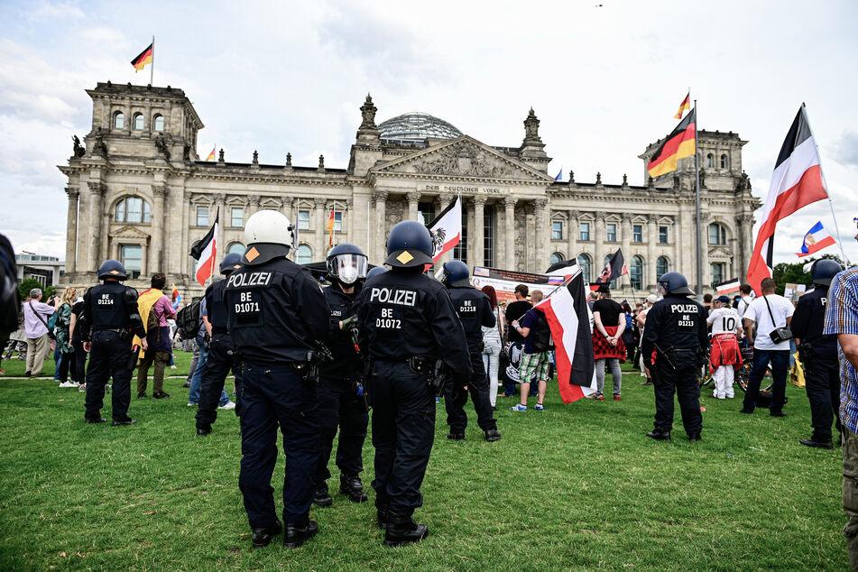 Teilnehmer einer Demonstration gegen die Corona-Maßnahmen stehen mit Reichsflaggen vor dem Reichstag