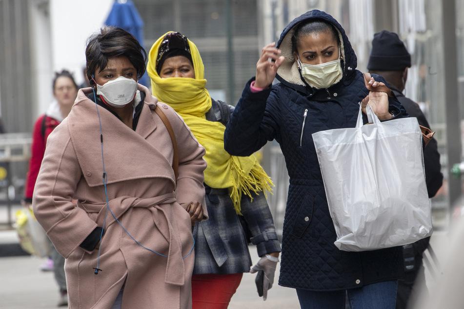 Afroamerikanische Frauen tragen auf ihrem Weg durch die 34th Street in New York eine Gesichtsmaske und einen Schal, um Mund und Nase zu schützen. Rapide steigende Zahlen von Corona-Infektionen und Todesfällen schrecken die USA auf.