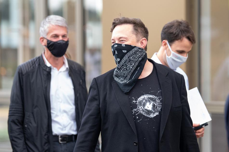 Technologieunternehmer Elon Musk (M) geht während seines Besuchs des Biotech-Unternehmens Curevac von einem Gebäude ins nächste.
