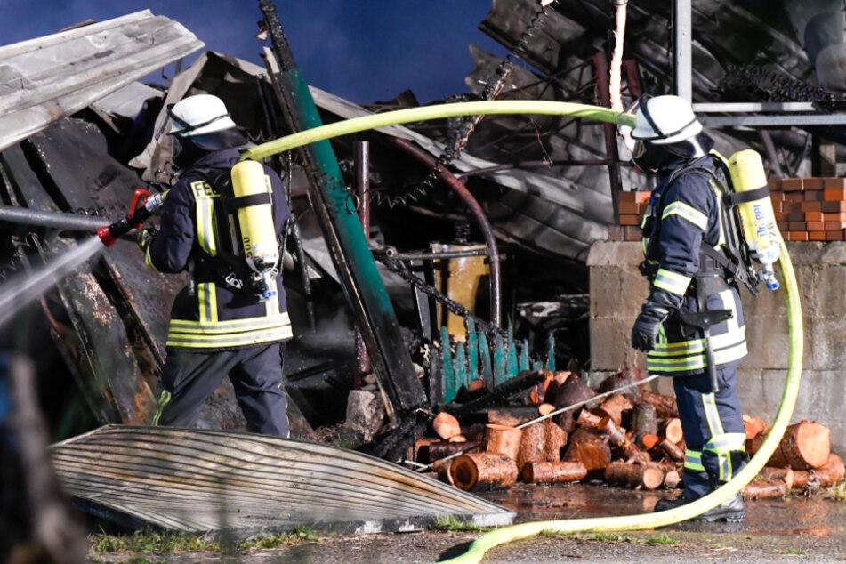 Feuerwehrleute löschen Glutreste in der eingestürzten Lagerhalle.