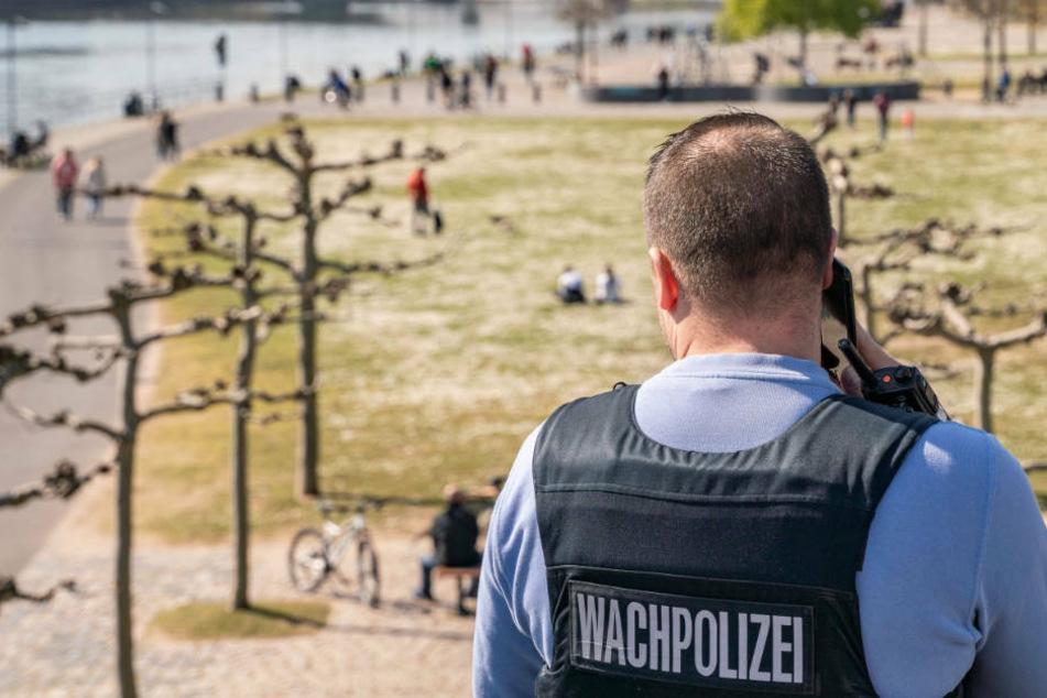 Ein Mitarbeiter der Wachpolizei überprüft am Nachmittag die Einhaltung der Kontaktsperre an der Weseler Werft am Mainufer.