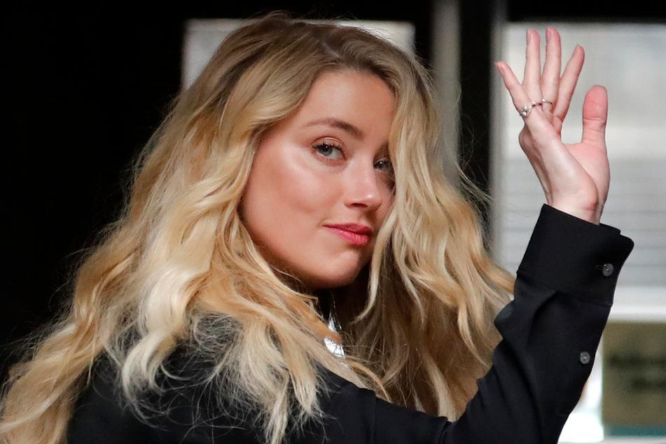 Die US-amerikanische Schauspielerin Amber Heard (34) winkt am Dienstag bei ihrer Ankunft in London am High Court .