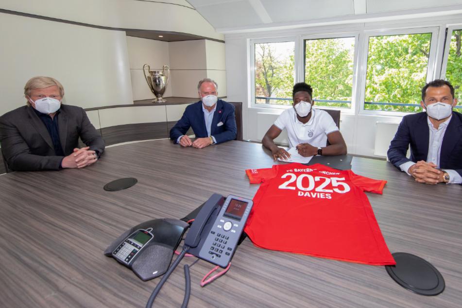 Oliver Kahn (v.l.n.r.), Vorstand des FC Bayern München, Karl-Heinz Rummenigge, Vorstandsvorsitzender des FC Bayern, Alphonso Davies und Sportdirektor Hasan Salihamidzic bei der Vertragsunterzeichnung.