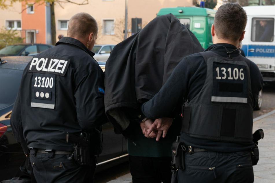 Nach einer Razzia im Clan-Milieu wird ein Verdächtiger von der Polizei abgeführt. (Symbolfoto)