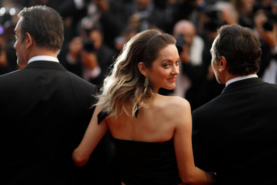 """Was wird nur aus dem Kino? Ein Bild aus goldenen Zeiten: Marion Cotillard, Schauspielerin aus Frankreich, steht vor der Premiere des Films """"La Belle Epoque"""" im Rahmen der 72. Internationalen Filmfestspiele eingehakt zwischen zwei Männern auf dem Roten Teppich."""