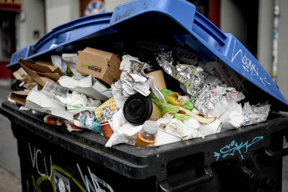 Eine überfüllte Mülltonne steht in Berlin am Straßenrand.
