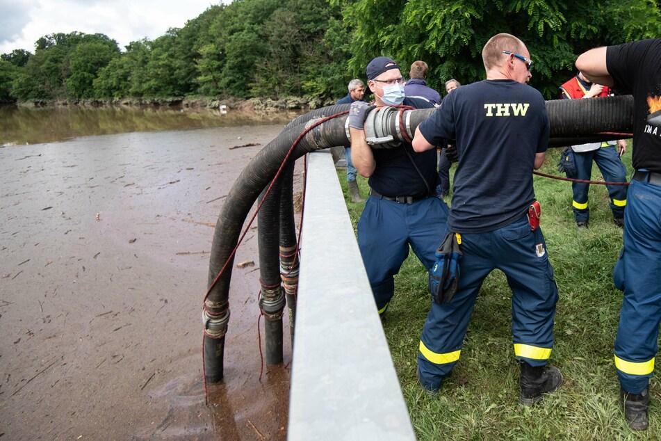 Euskirchen: Helfer des Technischen Hilfswerks (THW) lassen Schläuche in die Steinbachtalsperre hinab, um das Wasser abzupumpen.
