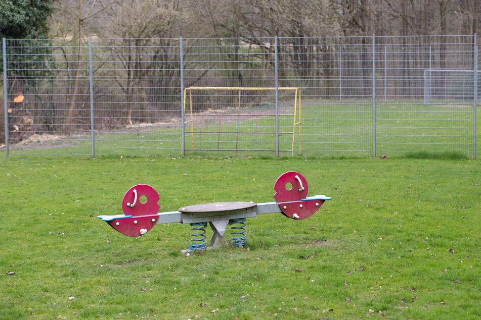 Eine Wippe und Fußball-Tore sind auf einem geschlossenen Spielplatz in Bielefeld zu sehen.