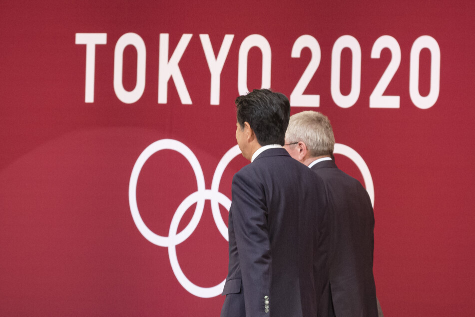 """Der Präsident des Internationalen Olympischen Komitees (IOC), Thomas Bach (r), und der japanische Premierminister Shinzo Abe nehmen an der """"One Year to Go""""-Zeremonie für die Olympischen Spiele 2020 in Tokio teil."""