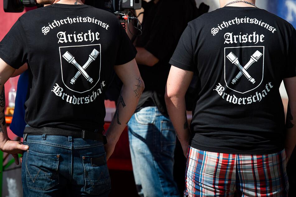 """2018. Zwei Männer tragen T-Shirts mit der Aufschrift """"Sicherheitsdienst Arische Bruderschaft"""" und Abbildungen von Stielhandgranaten stehen auf dem Gelände des Festivals """"Schild und Schwert""""."""