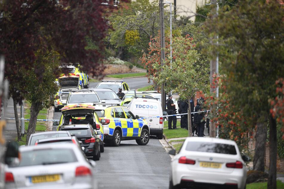 Bewaffnete Polizisten sichern nach einer Schießerei in der britischen Stadt Suffolk ein Grundstück.