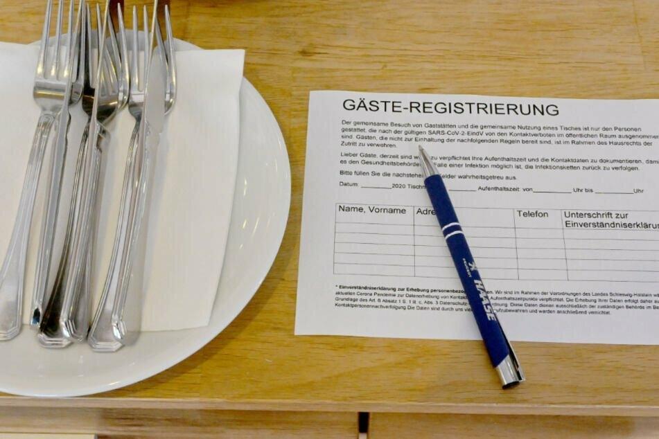 Gäste in Restaurants müssen ihre Kontaktdaten auf einen Zettel schreiben.
