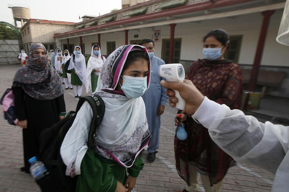 Pakistan, Peschawar: Eine Mitarbeiterin misst die Körpertemperatur von Schülerinnen bei deren Ankunft an einer Schule.
