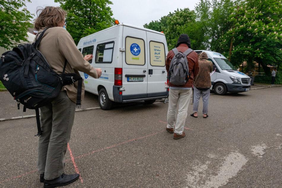 """Männer warten mit Abstand vor zwei weißen Behandlungsbussen der Organisation """"Ärzte der Welt"""" in München."""