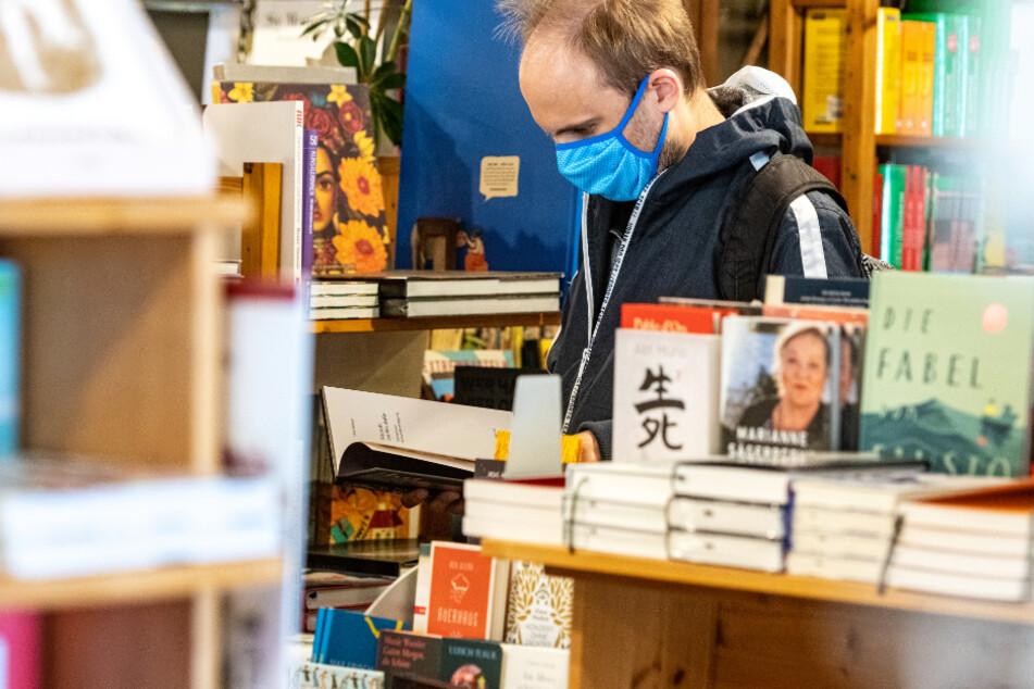 Ein Kunde steht mit Mundschutz in einem Buchladen.