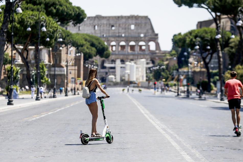 Touristen fahren mir E-Rollern auf das Kolosseum zu.