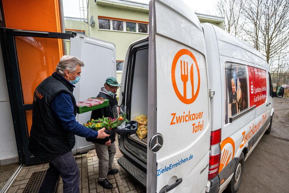 Tafelmitarbeiter verladen über die Stufen am Eingang Lebensmittel und Sachspenden in einen Transporter.
