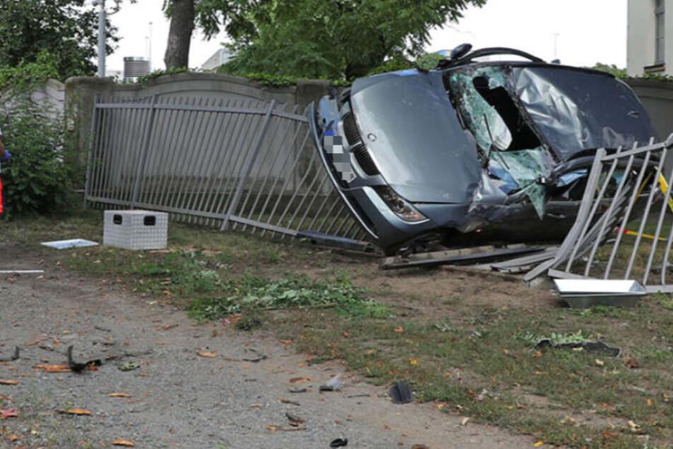 BMW schleudert gegen Baum und bleibt auf Polizeizaun hängen