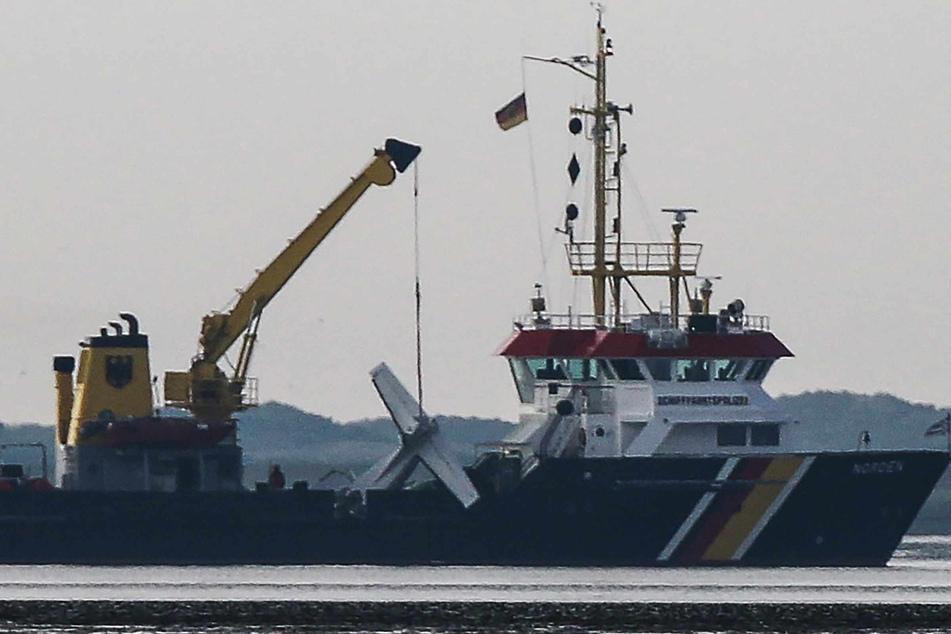 """Das Wrack einer verunglückten Cessna hängt am Kran an Bord des Tonnenlegers """"Norden"""" nahe der Absturzstelle im Wattenmeer vor der Insel Norderney"""