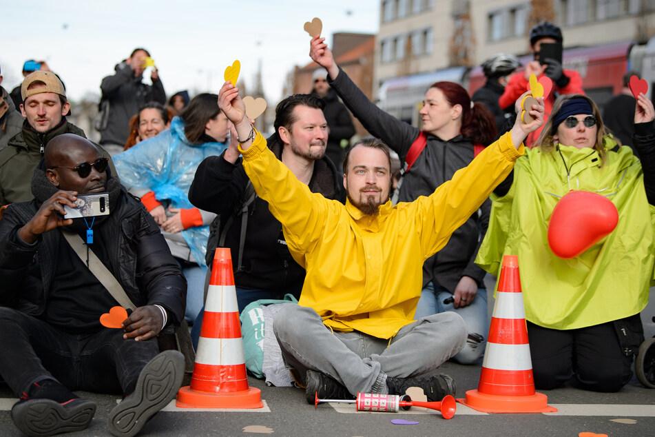 """Teilnehmer halten gelbe Papierherzen in der Hand und sitzen bei einer Kundgebung unter dem Motto """"Freie Bürger Kassel - Grundrechte und Demokratie"""" eng beieinander auf der Straße."""