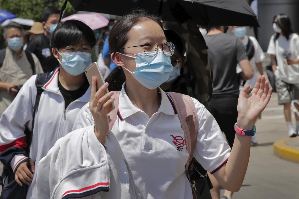 Eine Schülerin mit medizinischen Mundschutz klatscht als ist die Schule verlässt, am ersten Tag der nationalen Aufnahmeprüfungen für das chinesische College, bekannt als Gaokao. Die Aufnahmeprüfungen wurden aufgrund der Corona-Pandemie einen um Monat verschoben.