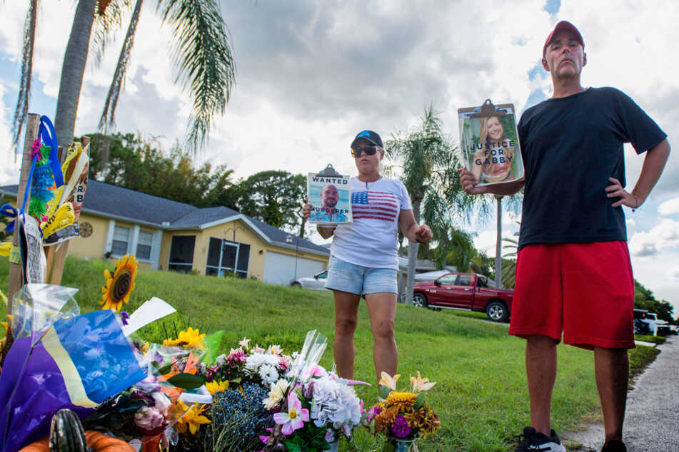 Two protesters stand by a makeshift memorial for Gabby Petito outside Brian Laundrie's parents' home in North Port, Florida on October 6.