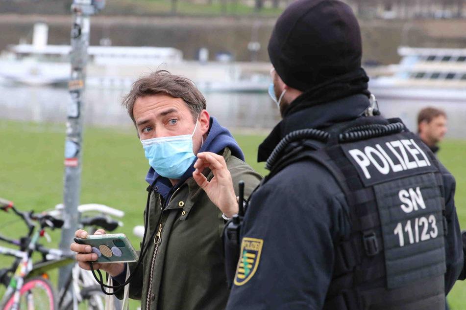 Immerhin mit Mundschutz: Rechtsextremist Sven Liebich diskutiert am Elbufer mit einem Polizisten.