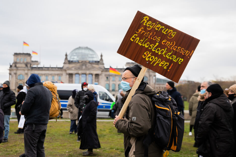 Ein Mann steht bei einer Kundgebung gegen die Corona-Maßnahmen vor dem Reichstagsgebäude