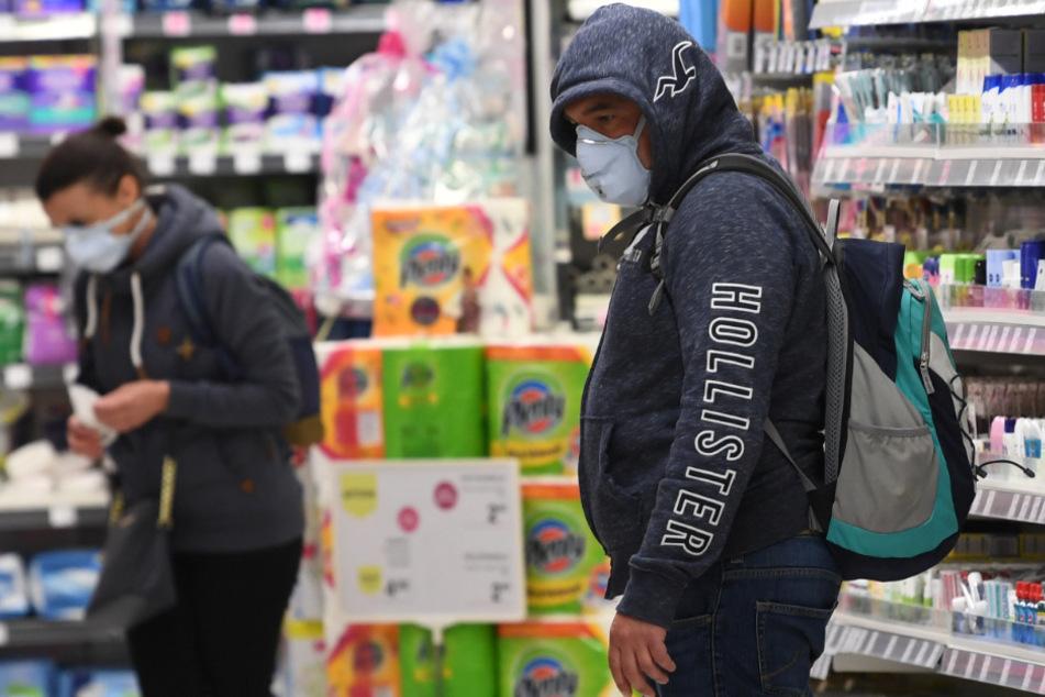 Kunden mit Mundschutz kaufen in einem Supermarkt ein.