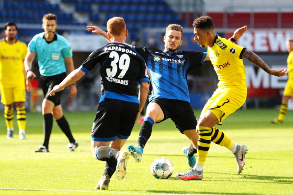 Der BVB tat sich lange schwer mit dem SC Paderborn. Hier wird Jadon Sancho von Dennis Srbeny (M.) und Sebastian Vasiliadis (l.) attackiert.