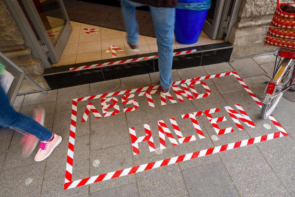 """Mit rotweißem Klebeband sind die Worte """"Abstand halten"""" vor einer Eisdiele auf das Pflaster geschrieben."""