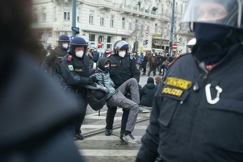Österreich, Wien: Polizeibeamte tragen einen Teilnehmer einer Demonstration gegen Corona-Maßnahmen weg.