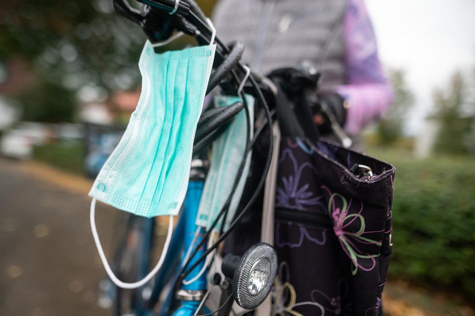 Eine Mund-Nasen-Bedeckung hängt an einem Fahrrad.