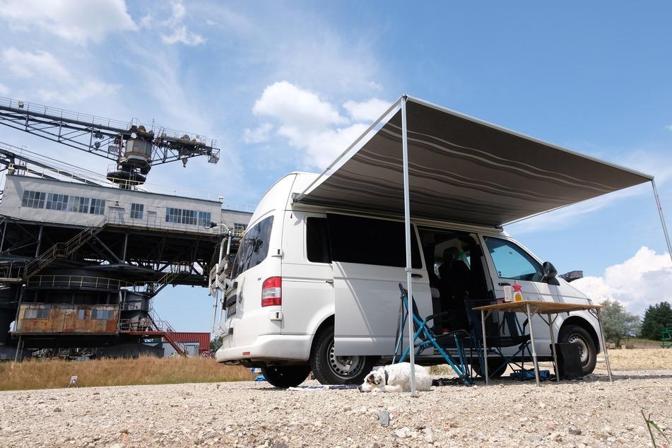 Ein Wohnmobil steht in Ferropolis vor ausgedienter Bergbautechnik.