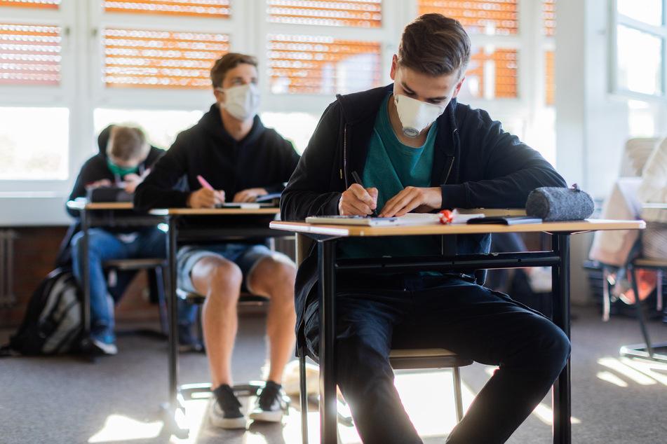 Archiv: Schüler und Schülerinnen des Abiturjahrgangs 2020 mit Masken im Unterricht.