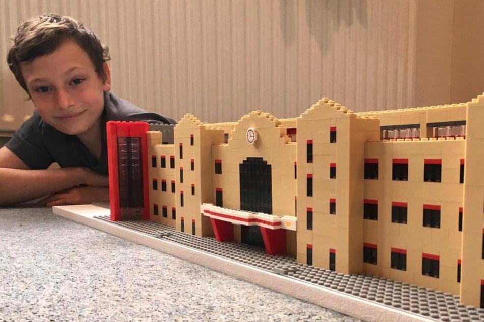 Joe Bryant (13) liegt neben seinem LEGO-Nachbau des Stadions An der Alten Försterei.