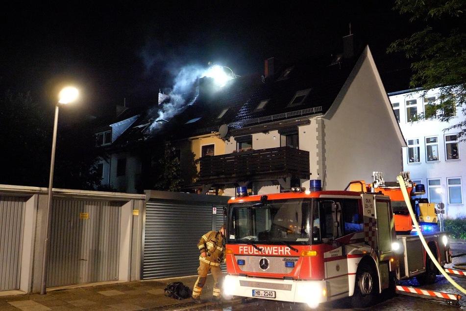 Die Feuerwehr im Einsatz. Rauch sein noch aus dem Dach des zuvor brennenden Hauses.