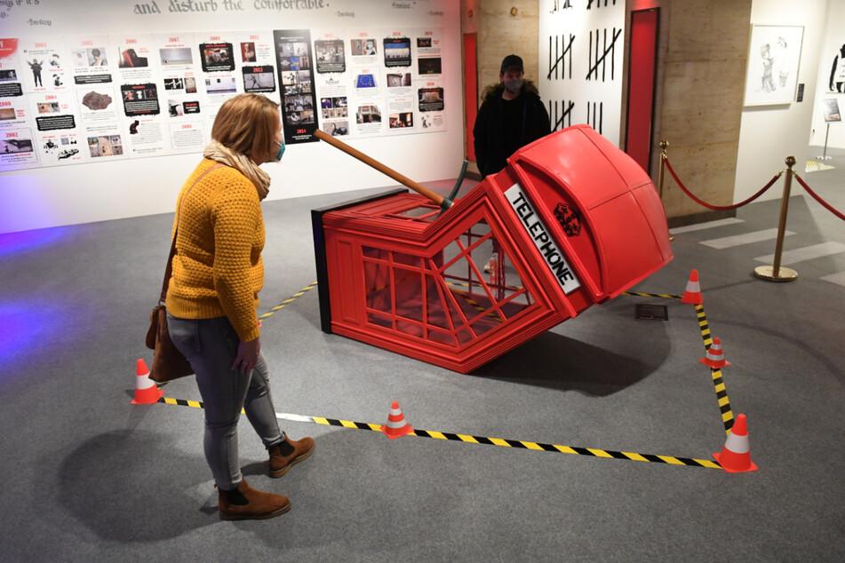 """Besucher betrachten in der Ausstellung """"The Mystery of Banksy – A Genius Mind"""" bei einem Presserundgang eine Reproduktion einer Arbeit des Künstlers Banksy mit dem Titel """"Death of a Phonebooth""""."""