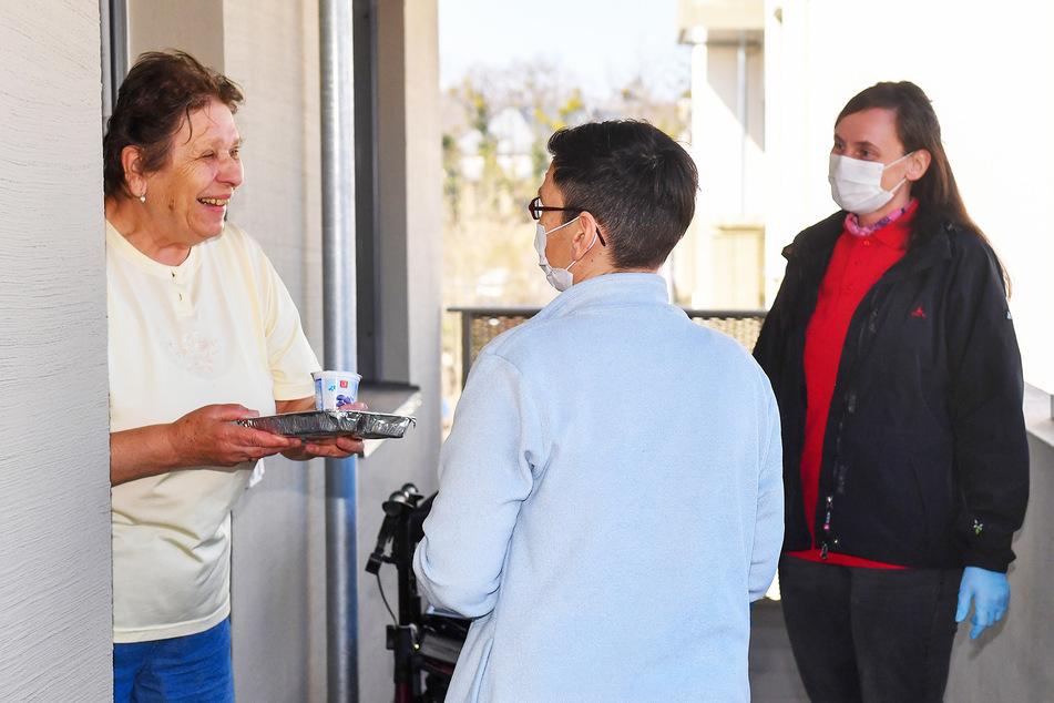 Guten Appetit! Mit Mundschutz und Handschuhen überreichen die Pflegerinnen der Rentnerin Helga Lachmann (80) ihr Mittagessen.