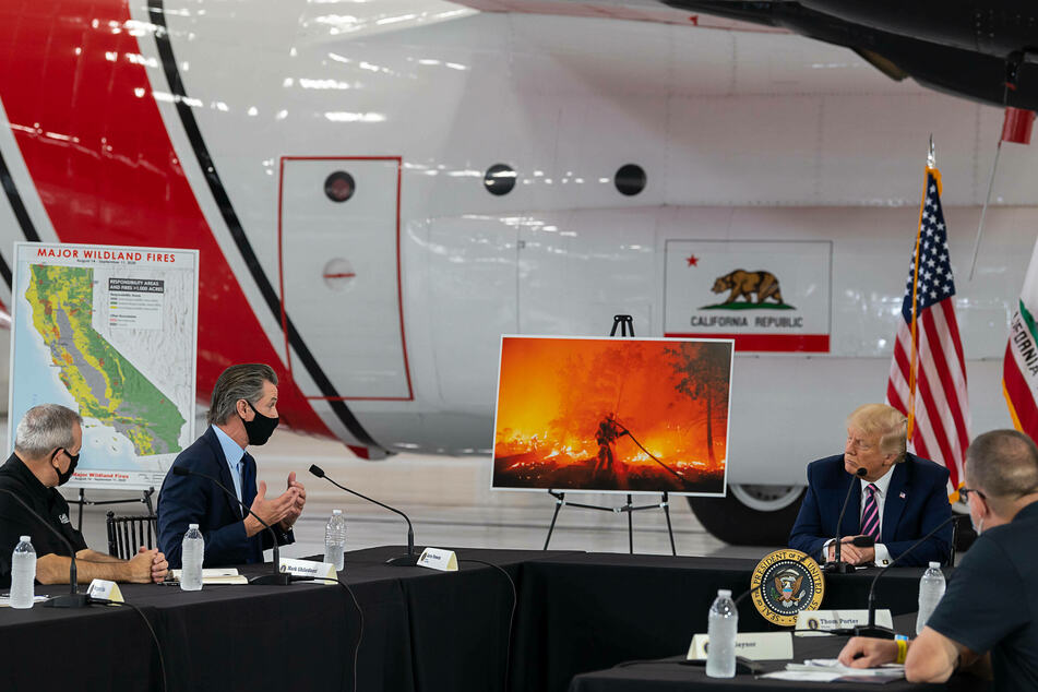 Donald Trump listening as California Governor Gavin Newsom talks about the forest fires in the West during a meeting at Sacramento's McClellan Airport.