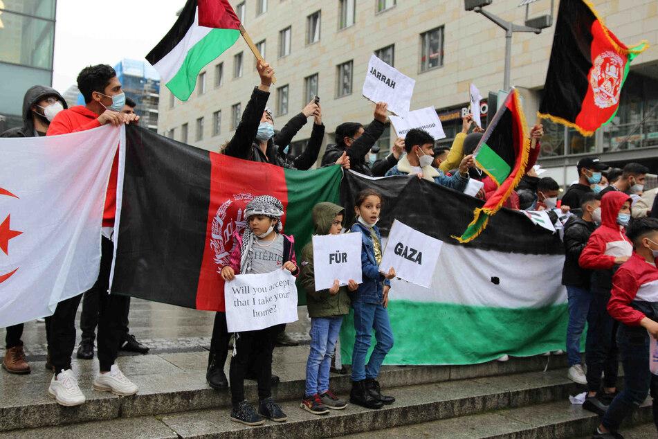 """Drei Kinder halten während der pro-palästinensischen Demonstration auf der Prager Straße Schilder mit den Aufschriften """"Will you accept that I take your home?"""" und """"Für Gaza""""."""