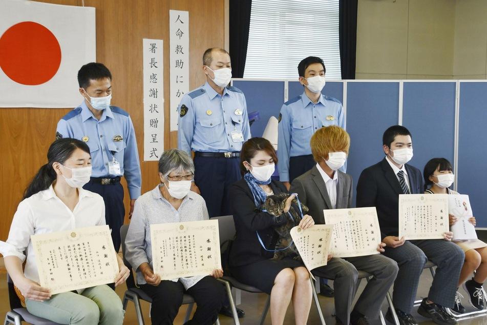 Tomoko Nitta (vorne, M) sitzt mit ihrem Kater Koko in der Polizeistation zwischen ihren Nachbarn. Auch diese hatten Dankesurkunden aufgrund der Rettung erhalten.