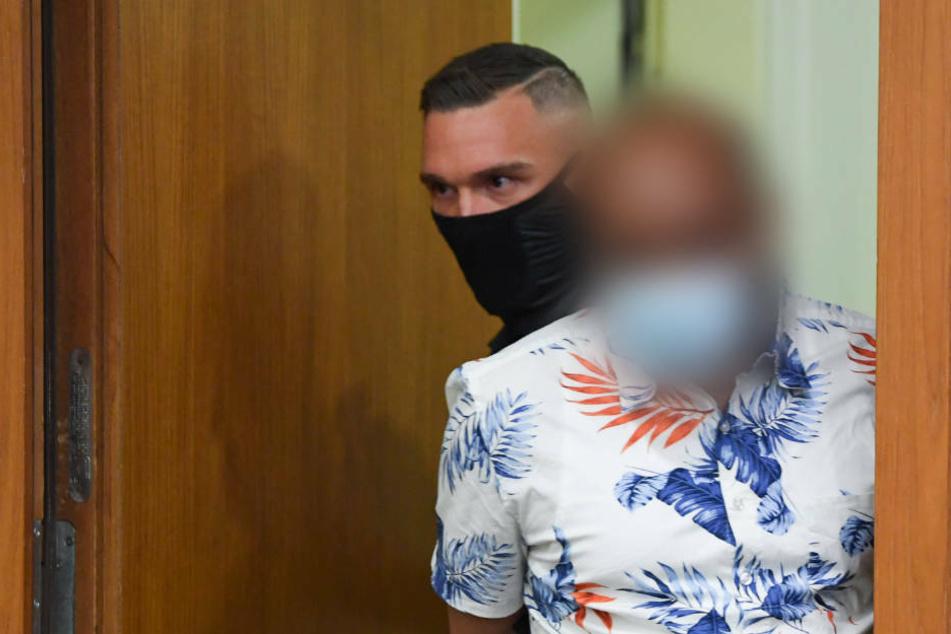 Ein Justizbeamter führt einen 41-jährigen Angeklagten (r) zum Prozessauftakt in den Gerichtssaal des Frankfurter Landgerichts.