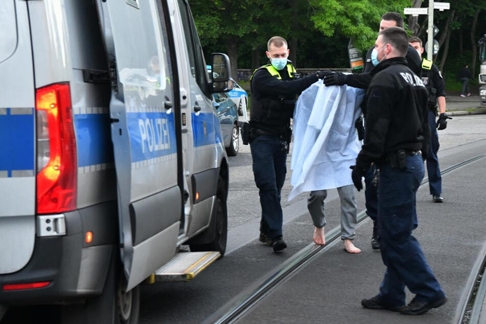 Polizisten führen den Verdächtigen ab.