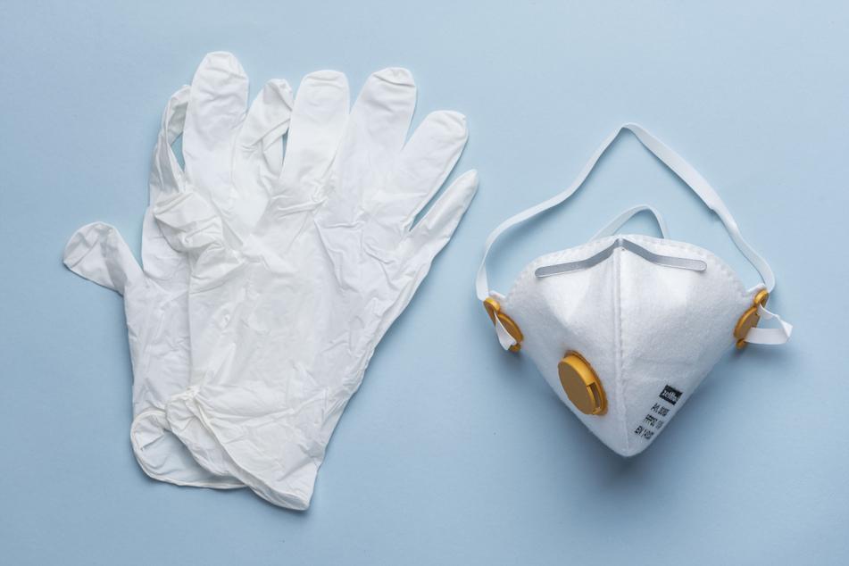 Eine Atemschutzmaske der Kategorie FFP3 und Einweghandschuhe.