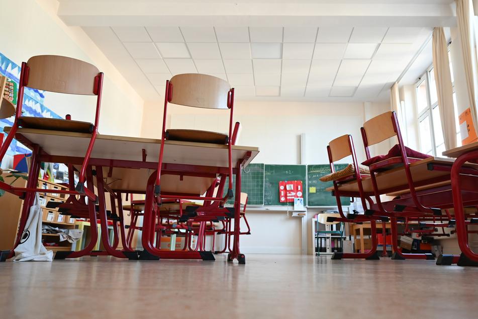 Stühle hängen in einem leeren Klassenzimmer auf den Tischplatten.