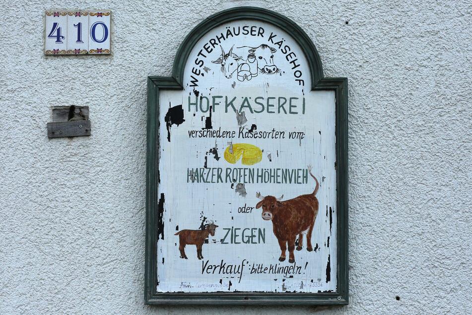 Eine Hinweistafel gibt Auskunft über das Angebot der Hofkäserei im Harz. Hier werden jährlich bis zu 3 Tonnen Käse verschiedener Sorten, darunter auch Harzkäse produziert.