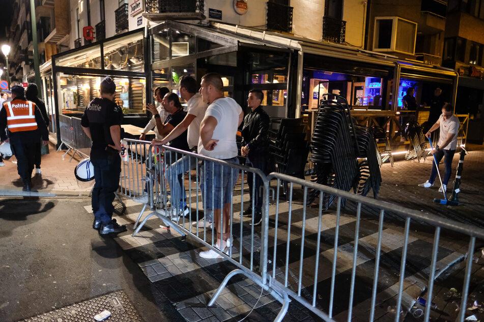 Männer diskutieren im Ausgehviertel mit einem Polizisten. In letzter Zeit haben feiernde Jugendliche, angeblich hauptsächlich Niederländer, nach der obligatorischen Schließung von Bars und Restaurants wegen der Corona-Pandemie für Ärger gesorgt.