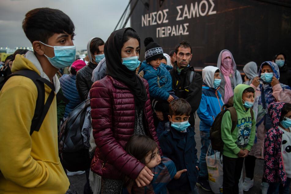 Menschen aus dem Flüchtlingslager Moria, die mit einem Schiff von der Insel Lesbos gekommen waren, stehen nach ihrer Ankunft im Hafen von Piräus bei Athen.