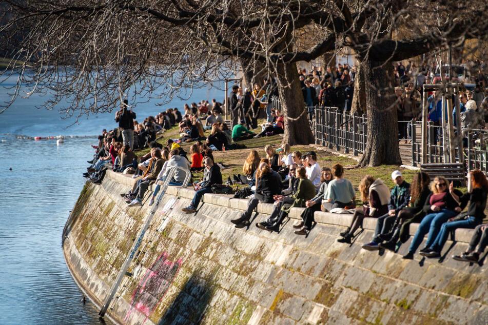 Menschen genießen am Landwehrkanal in Kreuzberg die Sonne.